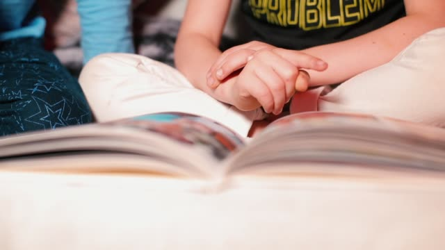 Closeup of the hands of a child turning over a page of a book.