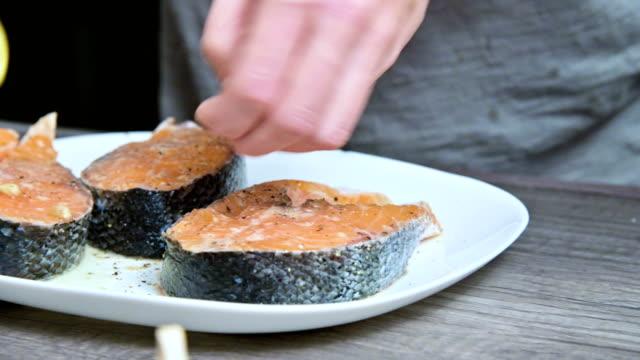 vídeos de stock, filmes e b-roll de close-up das mãos de uma cozinheira que prepara matruosa de salmão de peixe fresco regando com suco de limão. aperta as mãos de limões. o conceito de cozinhar cozinha caseira saudável e vegana - formato bruto