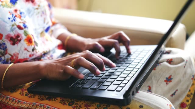Closeup of the hands of a woman wearing golden bangles and ring using a laptop