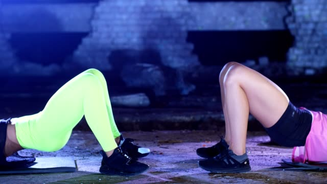 Close-up of the legs. Two athletic women, doing fitness exercises . At night, in light smoke, fog, in light of multicolored searchlights, in an old abandoned hangar Close-up of the legs. Two athletic women, doing fitness exercises . At night, in light smoke, fog, in light of multicolored searchlights, in an old abandoned hangar human back stock videos & royalty-free footage