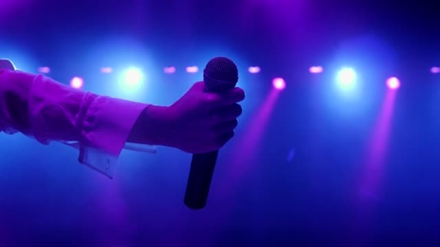 Close-up of the microphone in the singer's hand at an entertainment concert.