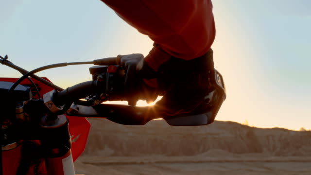 close-up of the motorcyclist's hand twisting throttle handle while standing on the scenic quarry off-road terrain in the sunset. - freestyle motocross video stock e b–roll