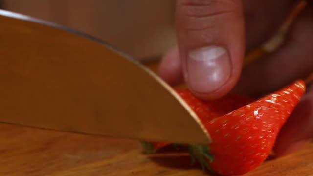Close-up of the process of cutting strawberry into quarters with a knife. Close-up of the process of cutting strawberry into quarters with a knife us coin stock videos & royalty-free footage