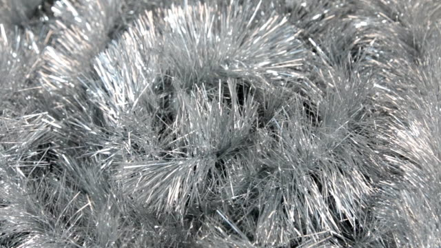 Close-up of the rotation of silver tinsel under the wind. Christmas background, tinsel. video