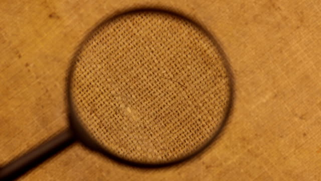Close-up of the rotation of the burlap cloth under the magnifying glass Close-up of the rotation of the burlap cloth under the magnifying glass. View from above canvas fabric stock videos & royalty-free footage