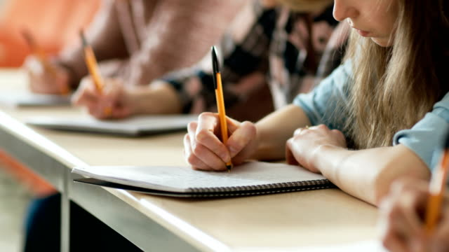 close-up of the row of students writing in the notebooks, taking exam. focus of hands with pens. - struttura pubblica video stock e b–roll