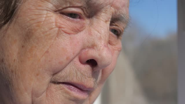 closeup of the sad face of an old woman suffering from tremor shaking eyelids - веко стоковые видео и кадры b-roll