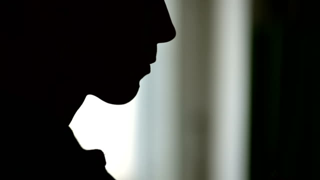 Close-up of the silhouette of a woman's face sticking a cigarette into her lips and igniting her with a lighter. The grim concept of the harm of smoking in a low key