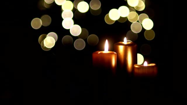 Nahaufnahme der drei Kerzen auf einem dunklen Hintergrund mit Weihnachtsbeleuchtung. Zwei Gläser mit Rotwein in der Hand, zwei feiern Weihnachten, Romantische Nacht treffen, Valentinstag – Video