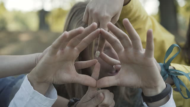 Close-up of three Caucasian hippies making peace sign with hands. Positive men and women expressing love and pacifism. Carefree young people and counterculture of the 1960s.