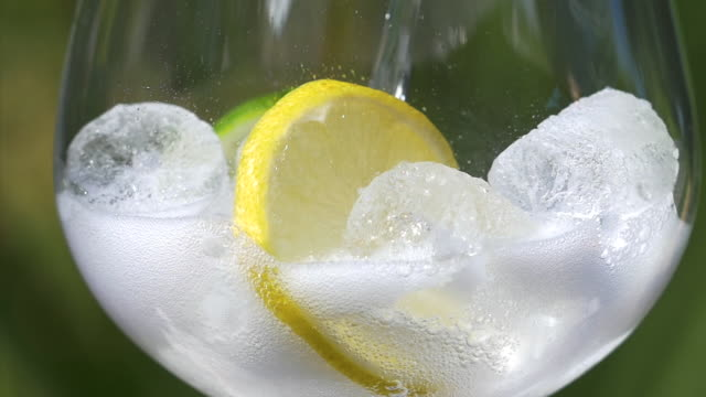 Close-up of tonic water pouring over ice, lemon and lime.