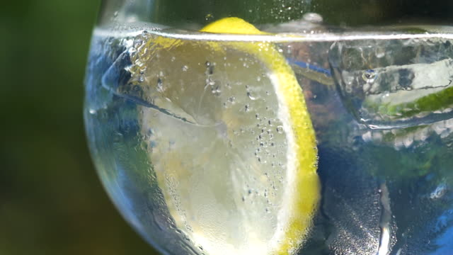 Close-up of tonic water with ice, lemon and lime. Slow motion pan L to R tonic water stock videos & royalty-free footage