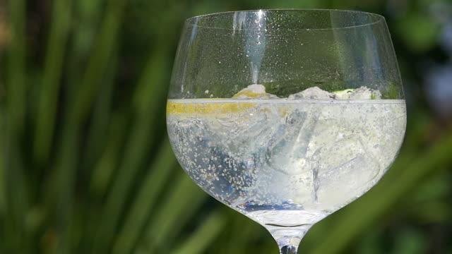 nahaufnahme der tonic wasser mit eis, zitrone und limette. - alkoholfreies getränk stock-videos und b-roll-filmmaterial