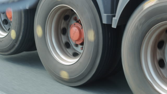 Closeup of truck tires rotating on highway road in slow-motion 4K video