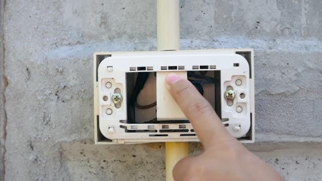 vídeos y material grabado en eventos de stock de primer plano de encendido y apagado de la luz de interruptor de pared desgastada en la pared de cemento. - descarga eléctrica