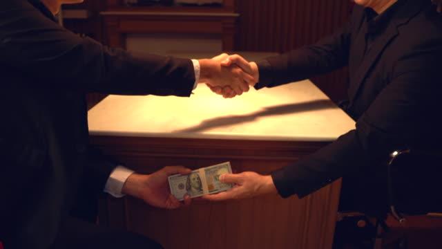 närbild av två företagare skakar hand och tar muta under trä table. hands passerar pengar under bord korruption mutor. - dirty money bildbanksvideor och videomaterial från bakom kulisserna
