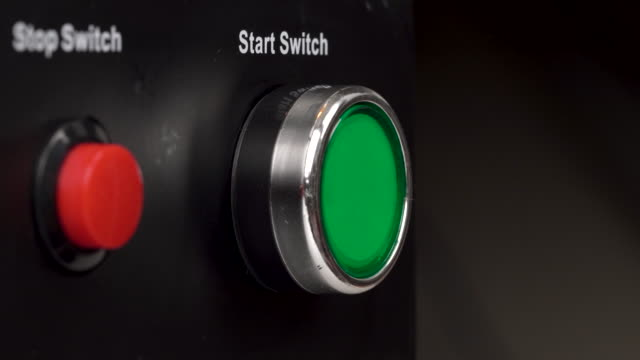 closeup of two buttons in the frame. green start switch and red stop switch buttons. finger press the green start switch button. - pchać filmów i materiałów b-roll