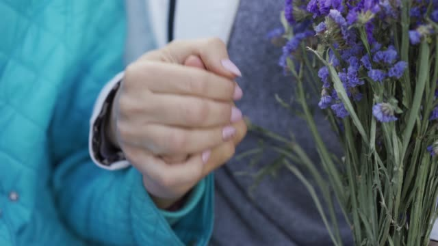 Close-up of two female hands holding each other. Younger and older women relationship. People holding a bouquet of wildflowers.