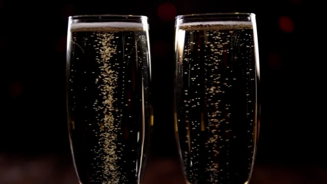 Close-up of two glasses of champagne with bubbles on a black background.