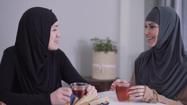 close-up of two happy muslim women talking and laughing indoors. female friends sitting at the table with tea and gossiping. culture, friendship, communication. - abbigliamento modesto video stock e b–roll