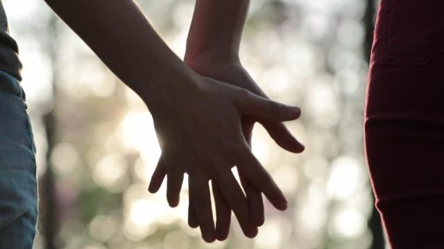 primo piano di due amanti lgbt che si uniscono alle mani in slow-motion con il bagliore del sole - mano umana video stock e b–roll