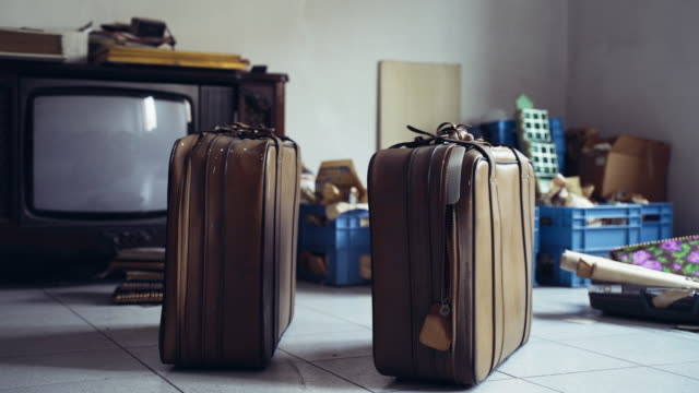 Close-up of two retro style travelling suitcases on the floor in old abandoned room among used unnecessary things. Suitcases are ready for leaving apartment, wrapped stuff boxes and old TV on background. Moving to new flat room