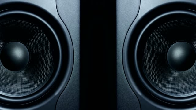 Close-up of two round audio sub-woofers vibrating video