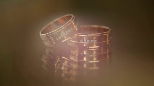 Closeup of two wedding rings with patches of light video