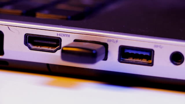 Closeup of USB flash drive inserted into port on the side of a laptop video