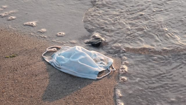 Close-up of used disposable face mask on the sandy beach in surf zone. Coronavirus (COVID-19) is contributing to pollution Seas and Oceans. Ecological pollution problem Close-up of used disposable face mask on the sandy beach in surf zone. Coronavirus (COVID-19) is contributing to pollution Seas and Oceans. Ecological pollution problem obsolete stock videos & royalty-free footage