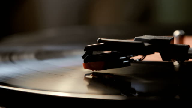 close-up of using an antiquarian vinyl record player. turntable player,dropping stylus needle on vinyl record playing - adulazione video stock e b–roll