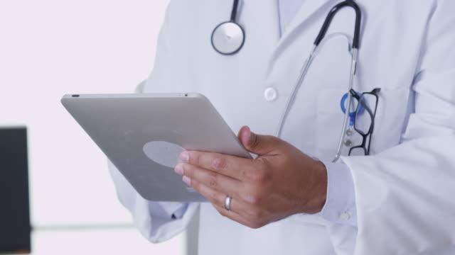 närbild av veterinär med hjälp av digitala tablett - veterinär, undersökning bildbanksvideor och videomaterial från bakom kulisserna