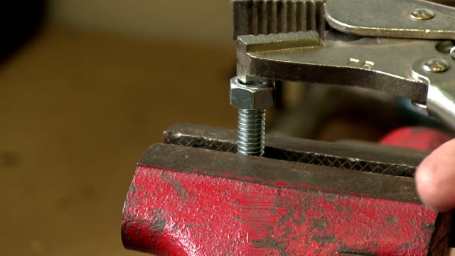 closeup of vice grips tightening nut on bolt with sound video