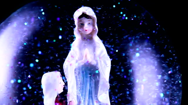 Close-up of virgin mary and a believer kneeled in a snow globe. The background is completely black. There is a lot a sparkling glitter in the snow globe.