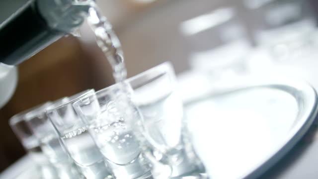 avvicinamento di vodka versato in un bicchiere da. - vodka video stock e b–roll