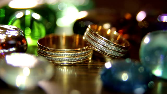Close-up of wedding rings on a bright background. Two wedding rings lie among brightly colored stones, close-up. brushed metal stock videos & royalty-free footage