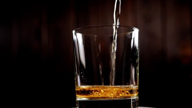 close-up of whiskey poured into a rotating glass on a black background. - whisky video stock e b–roll