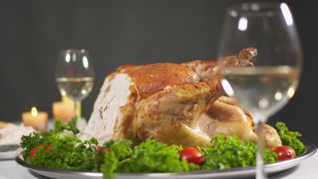 closeup of whole roasted turkey garnished with tomatoes and herbs - indyk pieczony filmów i materiałów b-roll