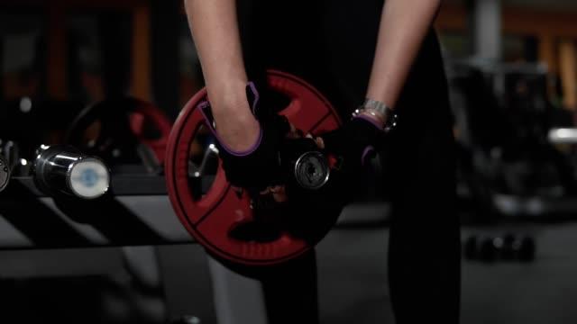 nahaufnahme der frau fügen teller auf die langhantel in dunklen fitnessraum vor dem training - turngerät mit holm stock-videos und b-roll-filmmaterial