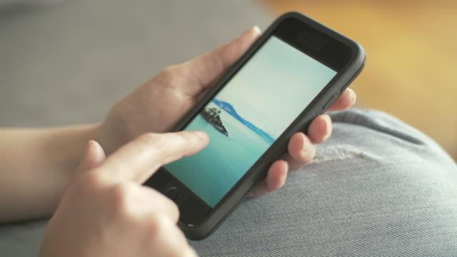 closeup of woman browsing beach photographs on smartphone - tap water filmów i materiałów b-roll