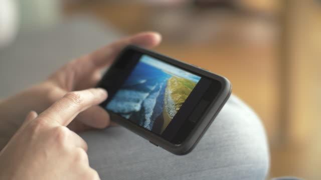 closeup of woman browsing beach photos on smartphone - tap water filmów i materiałów b-roll