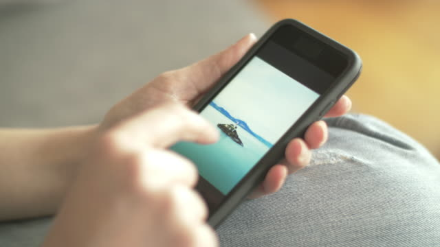 closeup of woman browsing beach pictures on smartphone - tap water filmów i materiałów b-roll