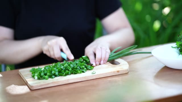 close-up of woman cutting green onion on wooden board outdoors. women's hands cutting verdure with knife on chopping board - rodzina czosnkowatych filmów i materiałów b-roll