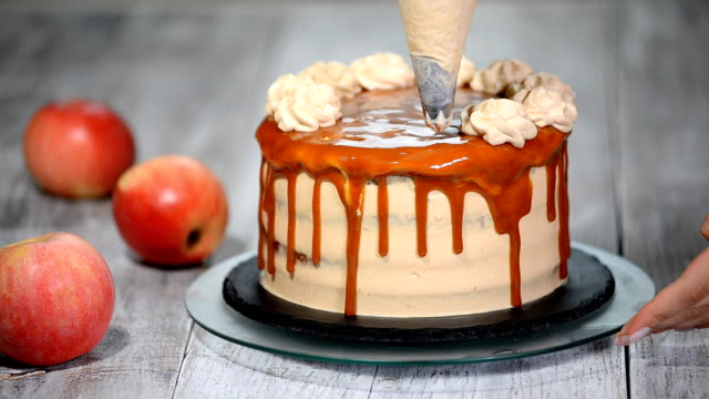 Close-up of woman decorating cake. Making Caramel Apple Cake.