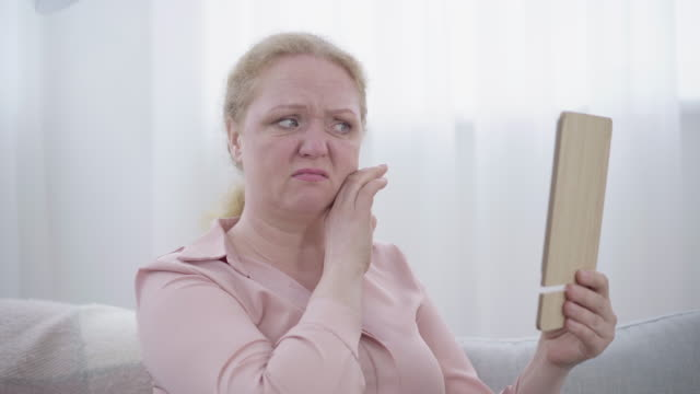 Close-up of woman examining wrinkles on face. Side view of senior Caucasian lady dissatisfied with reflection in hand mirror. Aging, femininity, lifestyle