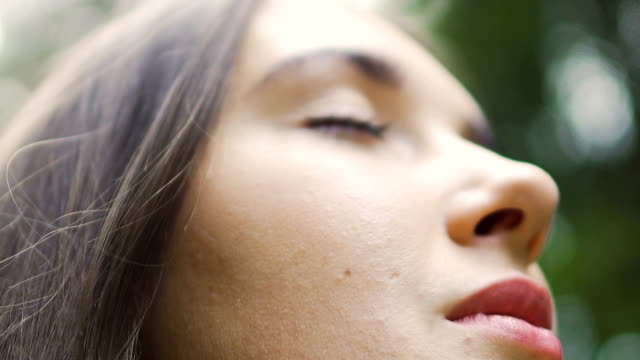 close-up of woman face outdoors closed eyes, woman meditates in park slow motion - woman portrait forest video stock e b–roll