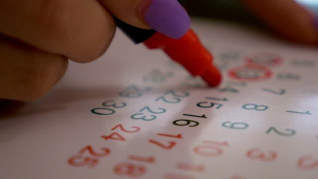 vídeos de stock, filmes e b-roll de closeup, mão de mulher marcando datas e dias calendário com marcador vermelho - calendário