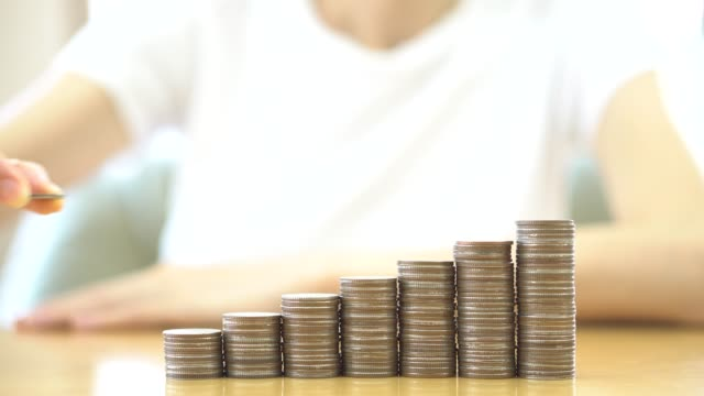 Close-up Of woman Hand Put Coins To Stack Of Coins