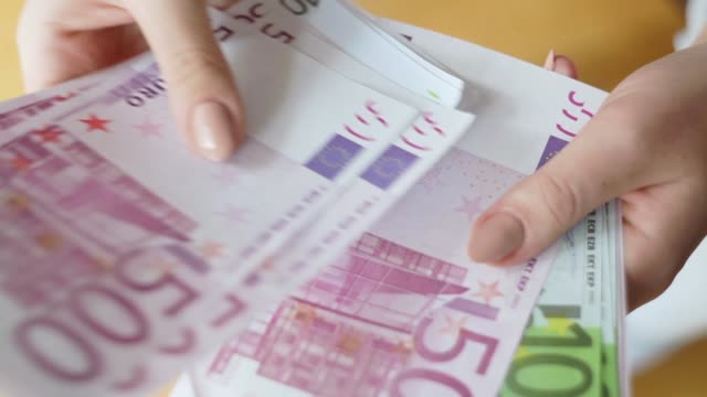Closeup of woman hands counting new 100 and 500 euro banknotes