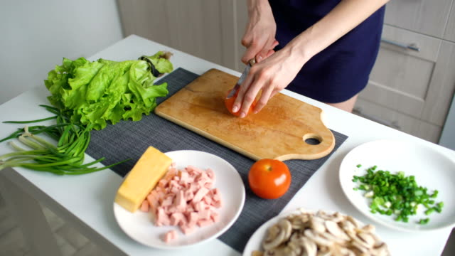 Closeup of woman hands cutting red tomato on wooden board for pizza in the kitchen at home video